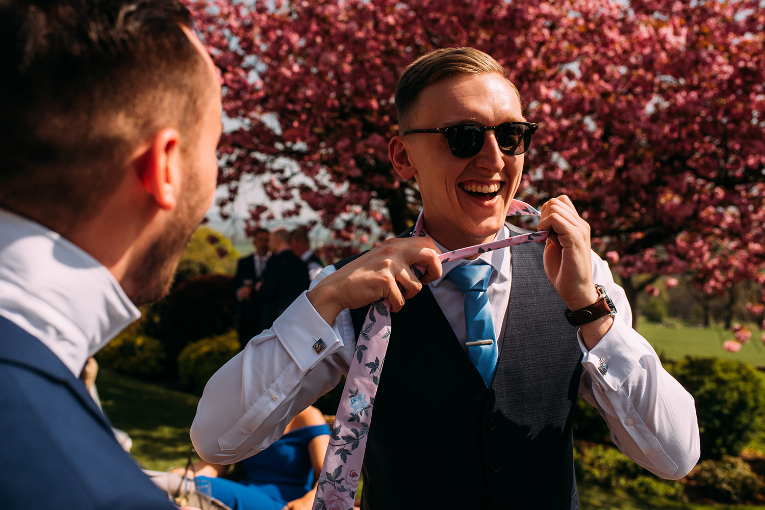 wedding guest laughing and pulling his tie over his head