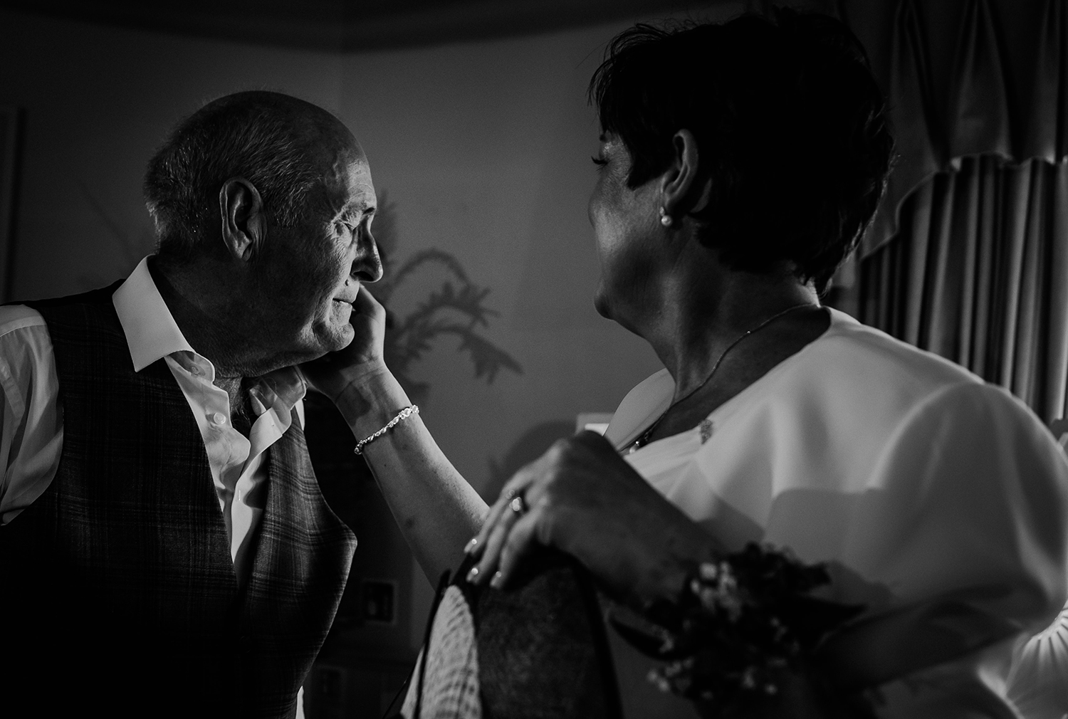 bw photo of emotional father of the groom. The brides mother has her hand on his cheek to comfort him