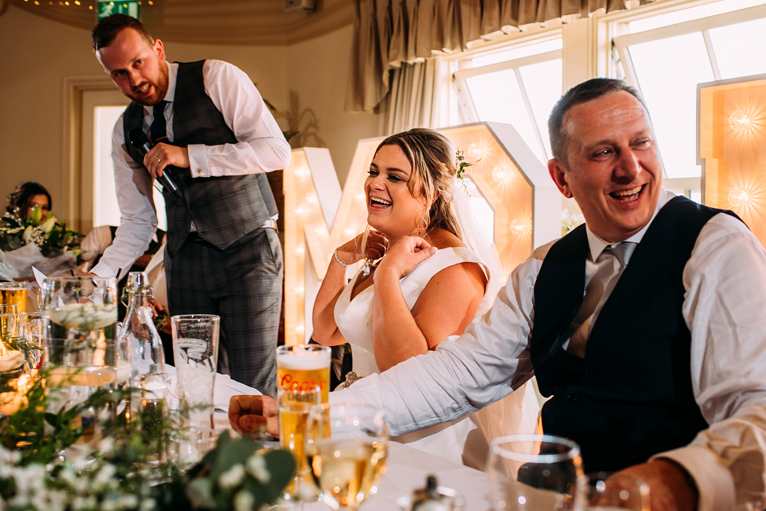 bride and her father laughing during the grooms speech