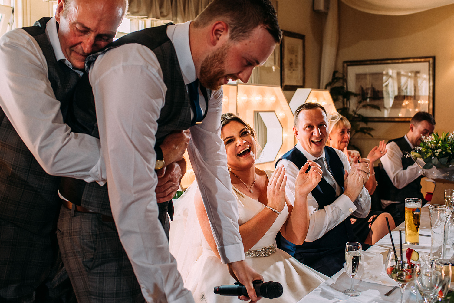 groom emotional during his speech so his father gives him a hug as he struggles
