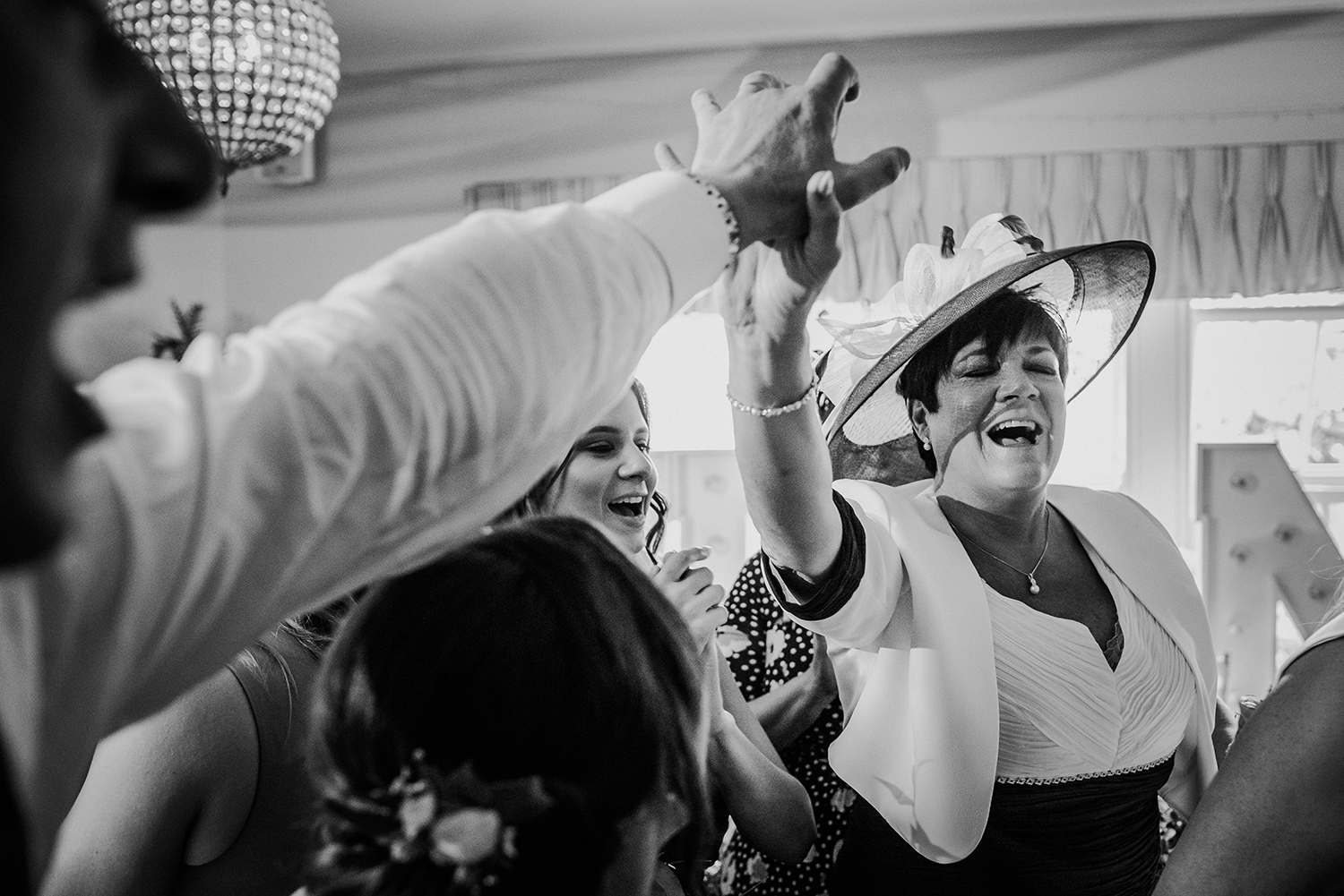 bw photo. Bride's mother holding hands in the air and singing. Emotional tribute to a lost relative