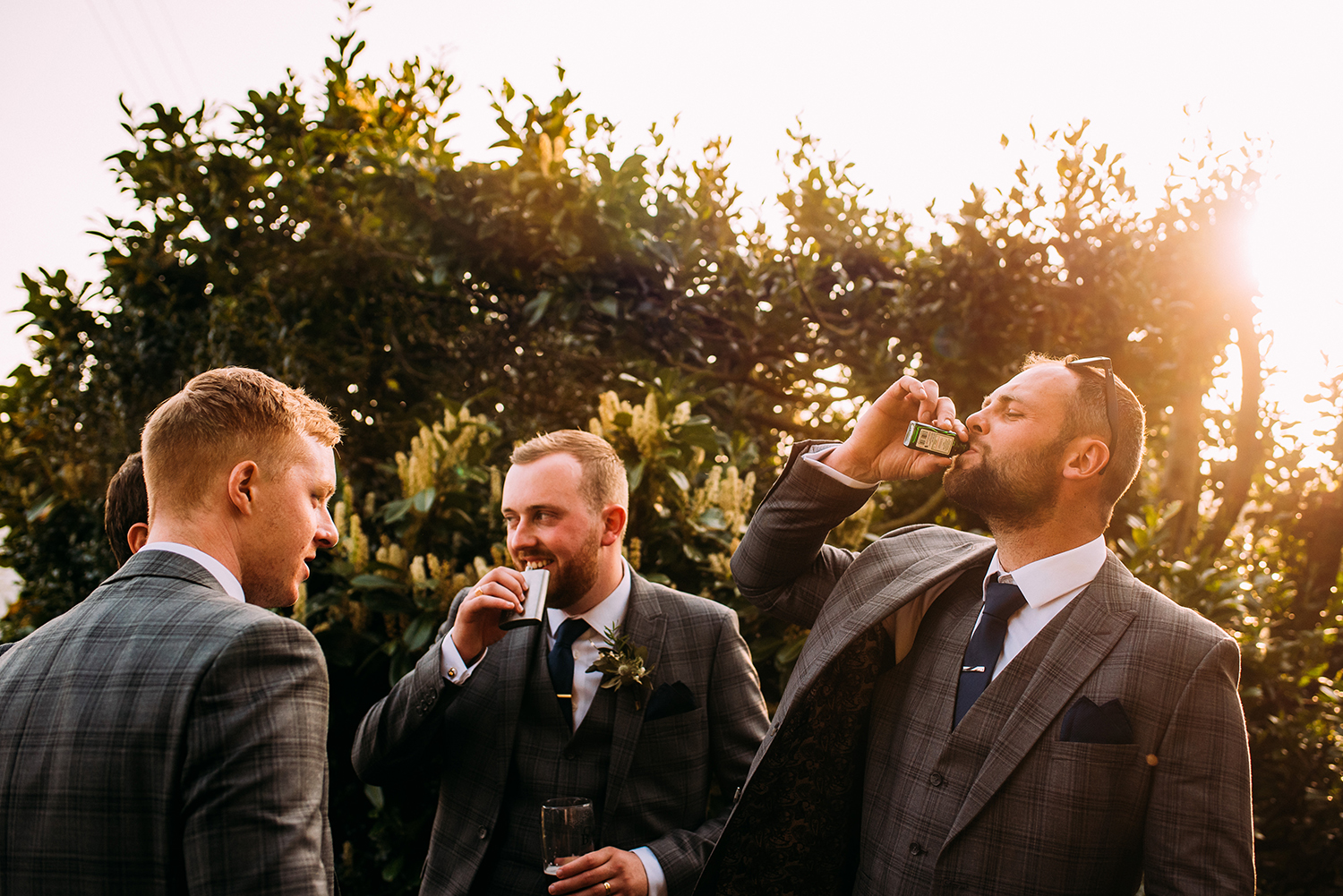 Groomsmen drinking out of a flask in the evening sun light
