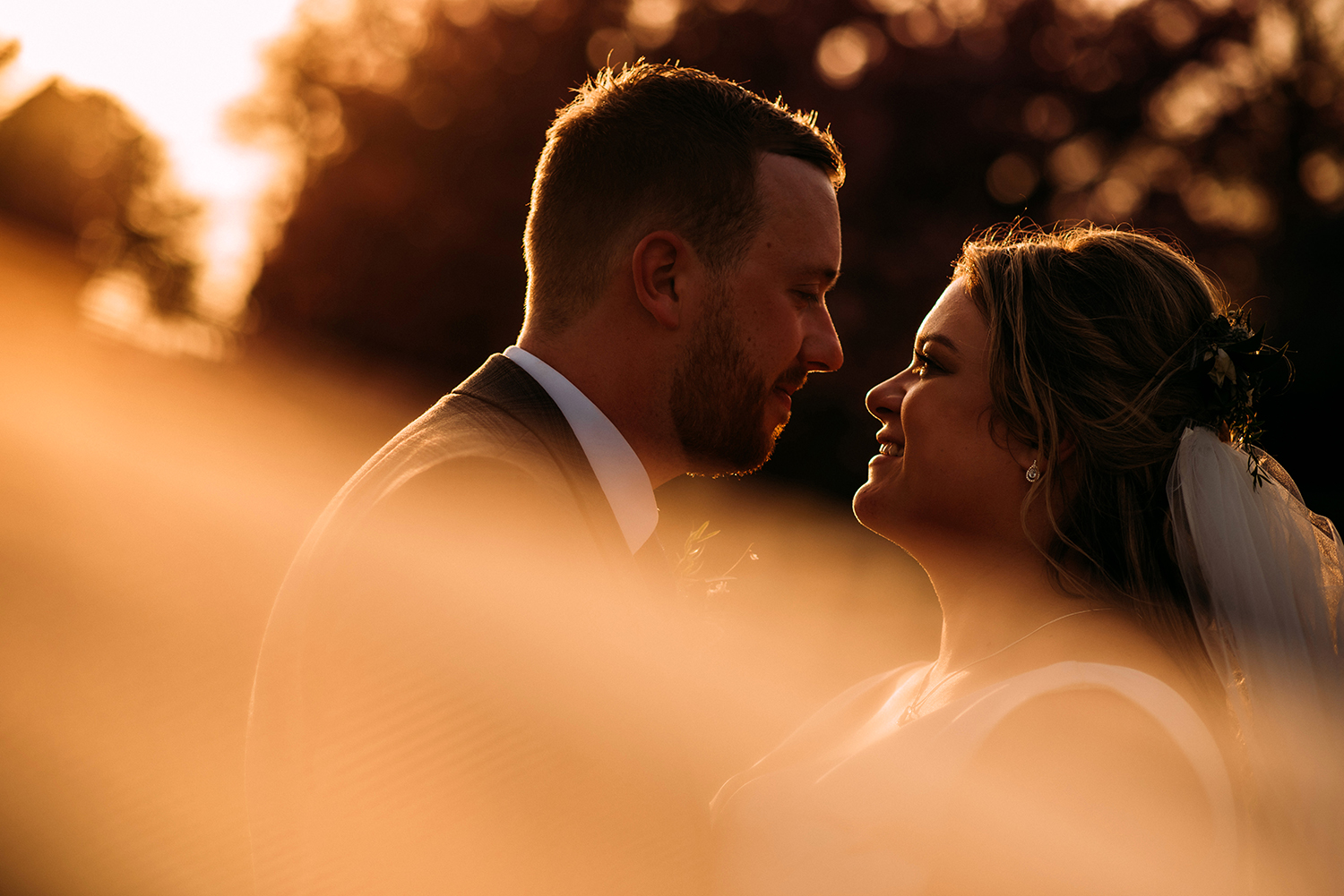 Shot of the bride and groom through the veil in the evening sun light