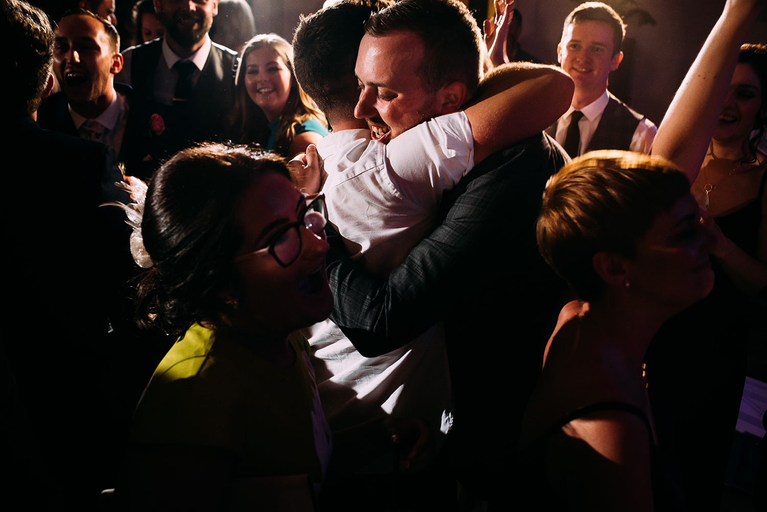 groom hugging his friend on the dance floor