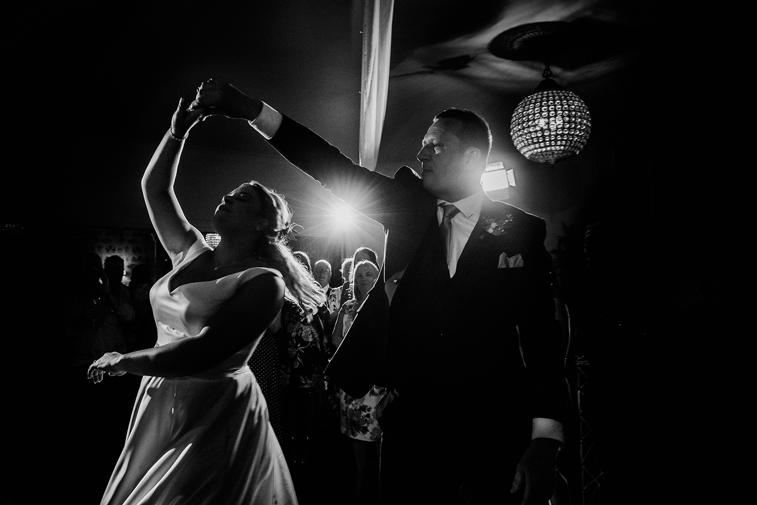 bw photo of the bride twirling while dancing with dad