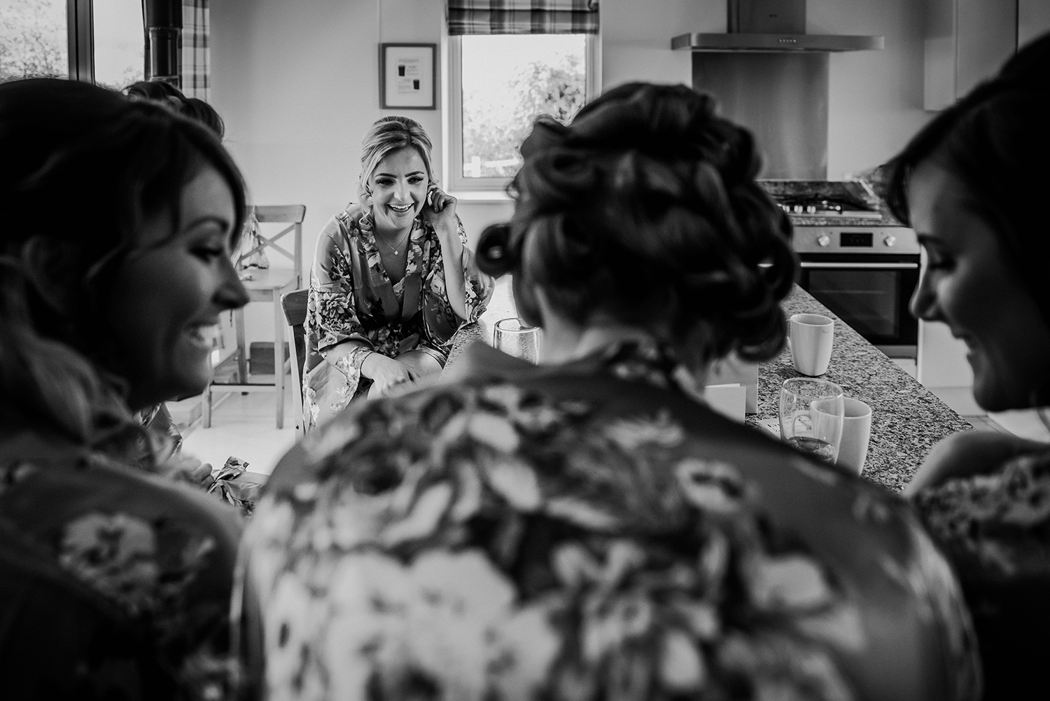 BW photo of the bridesmaids having a laugh in the kitchen