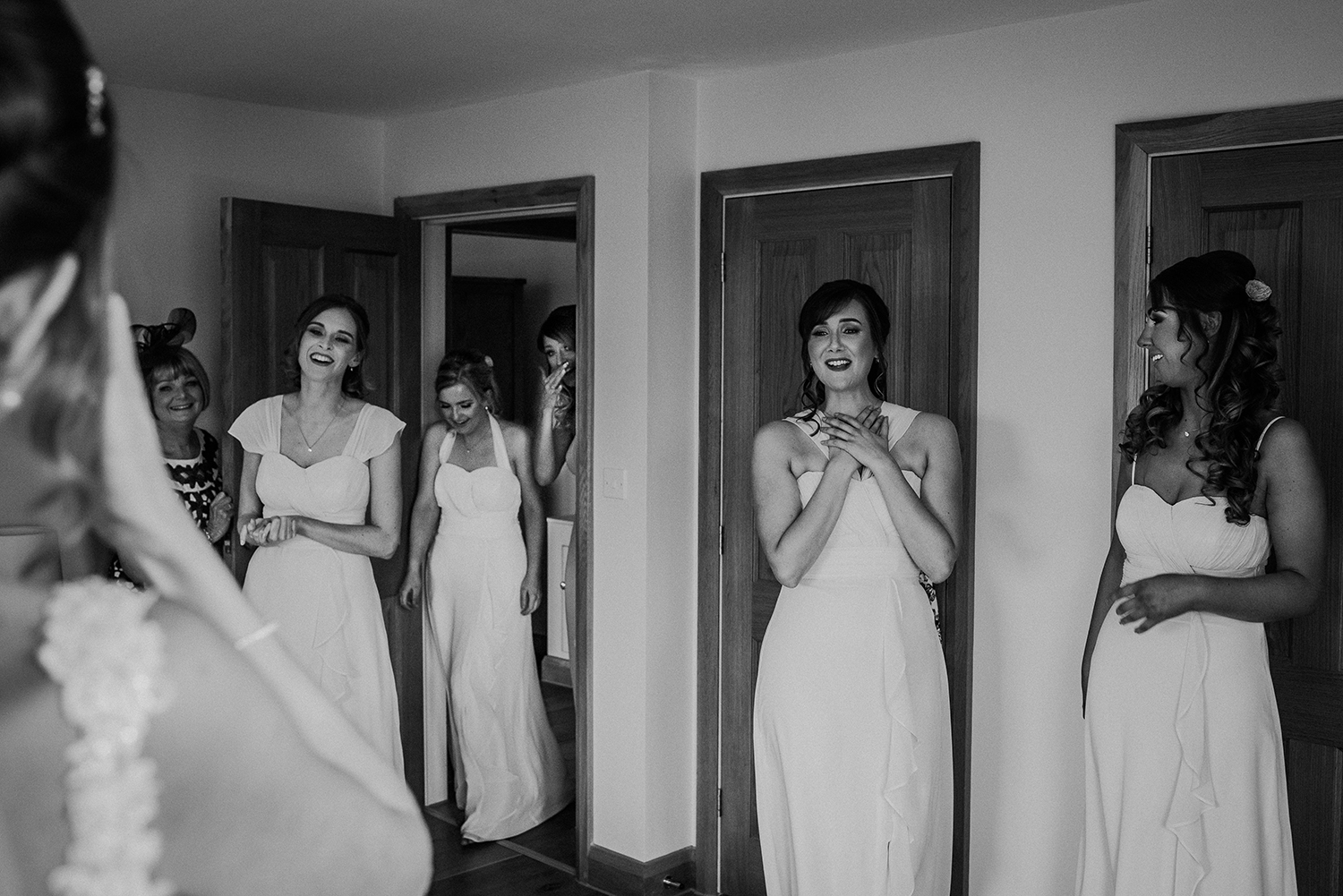 bw photo of the bridesmaids reaction to the bride in her dress