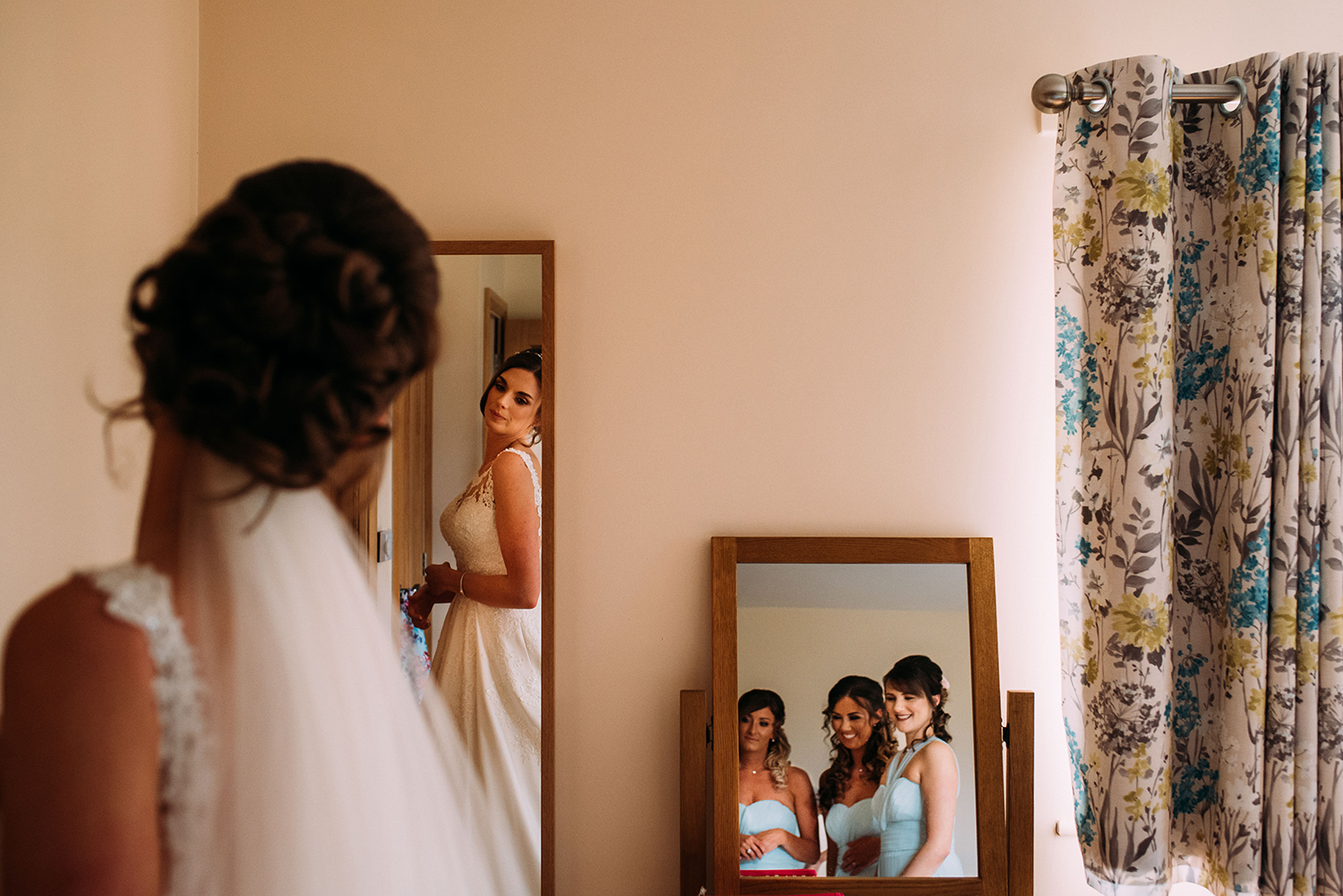 bride looks at her reflection in the mirror, the bridesmaids reflection can be seen in another mirror to the right