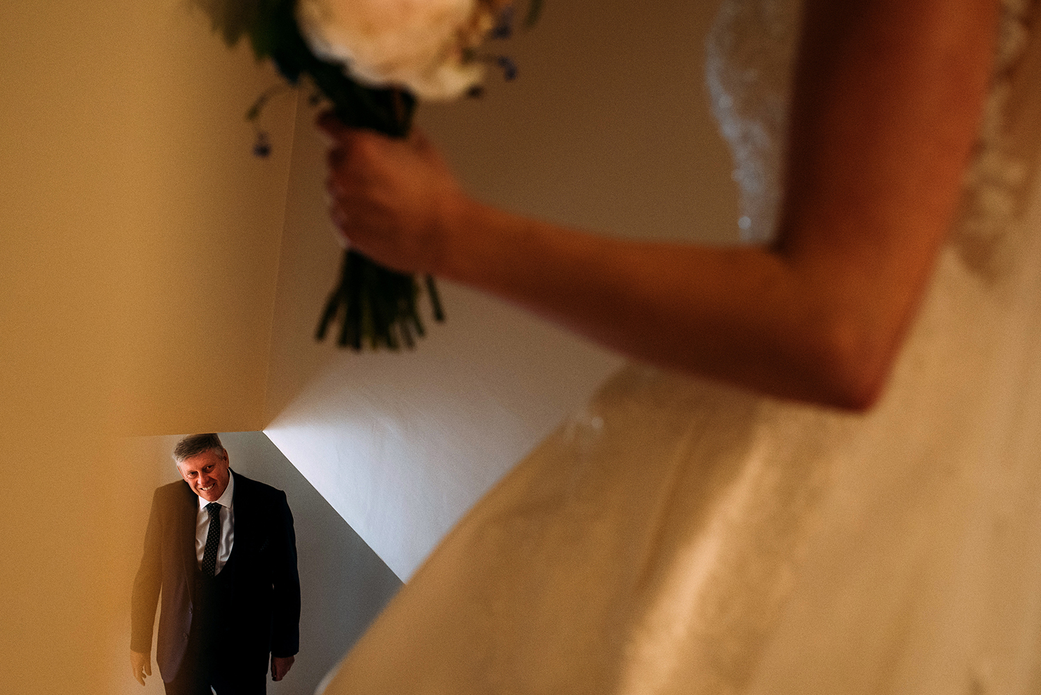 Bride walking down the stairs. Her fathers reaction can be seen in the bottom left of the frame
