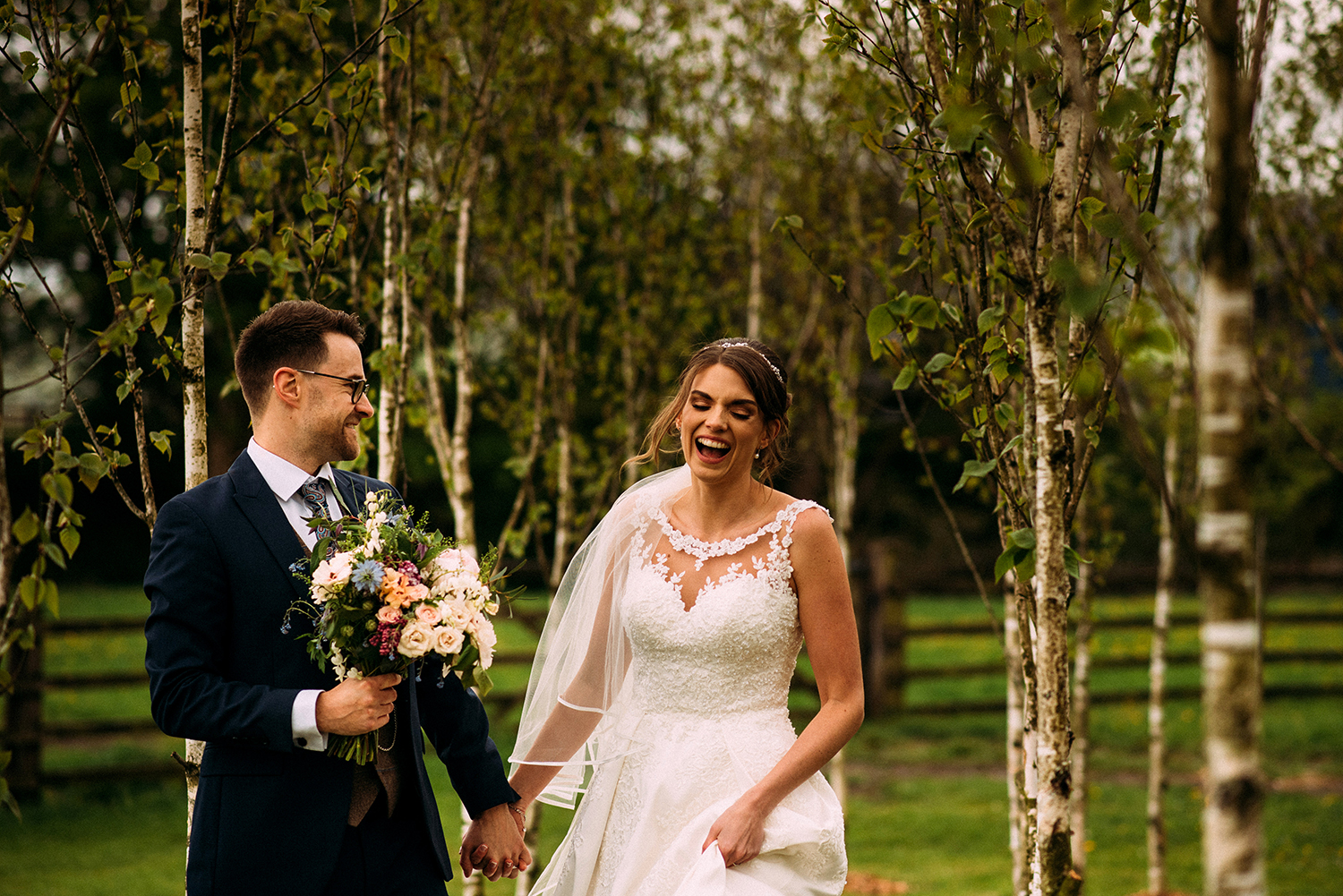 Bride and groom walking and laughing together at the Out barn wedding venue