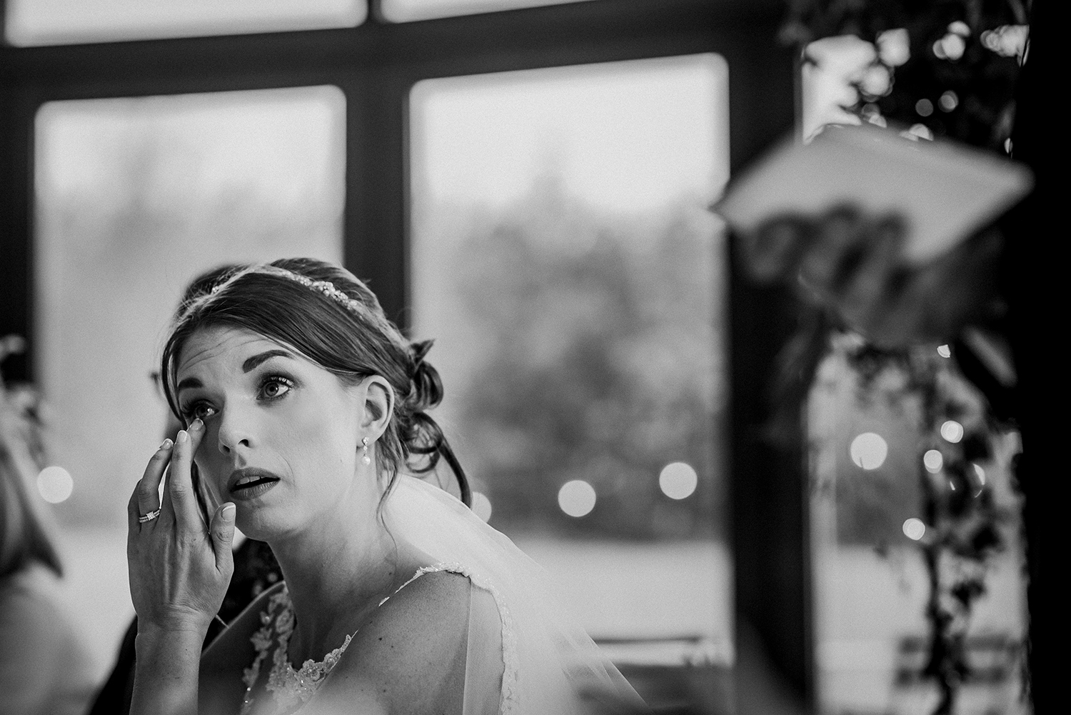 BW photo of the bride wiping a tear from her eye during the speeches