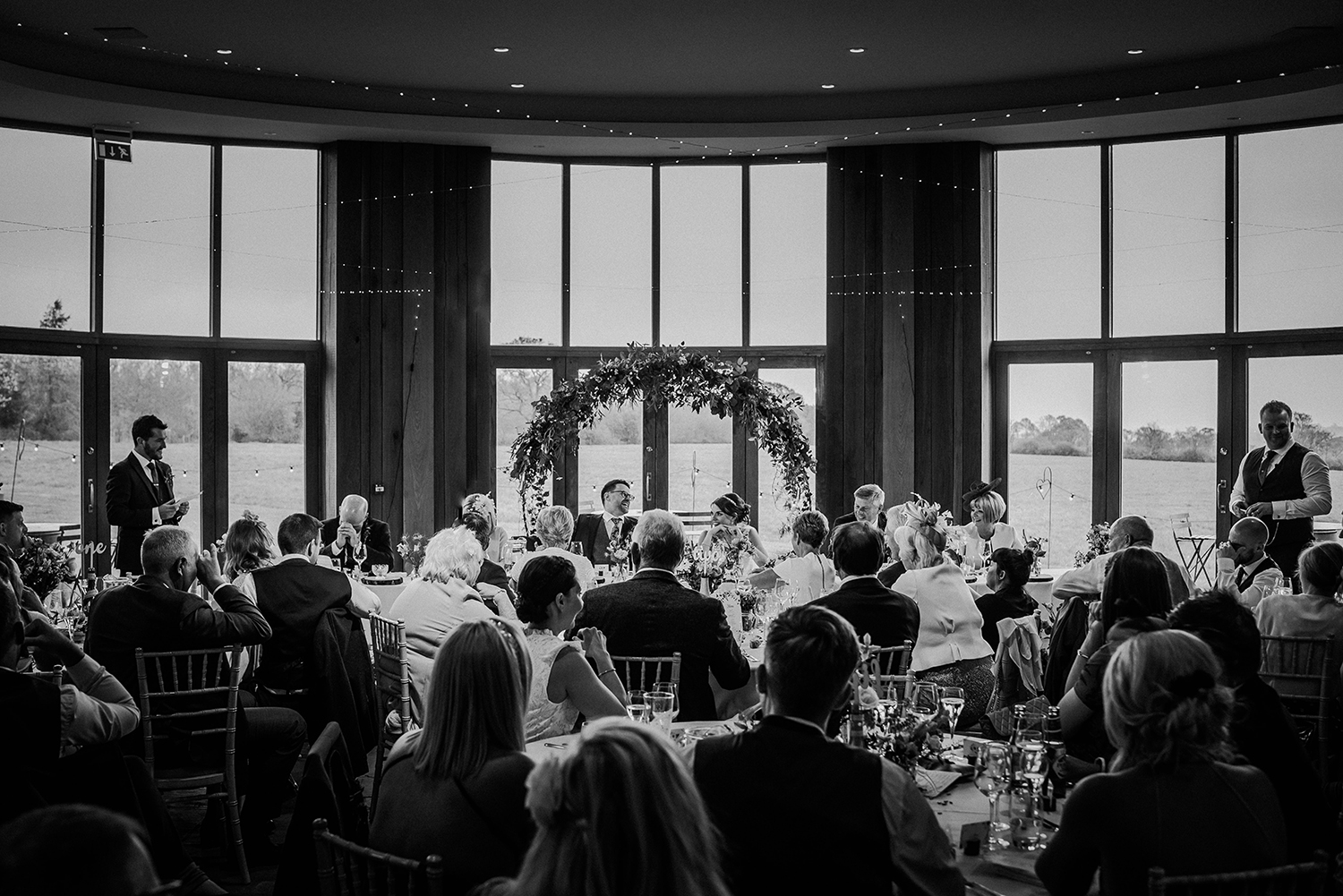 Wide BW shot of the Out Barn ceremony room during the best men speech