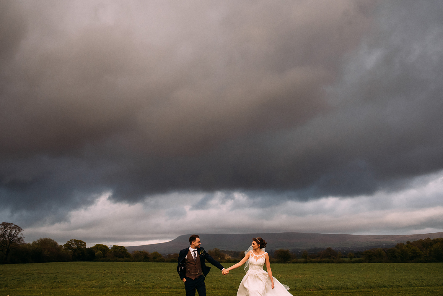 Bride and groom walking up the fields at the Out Barn with Pendle hill in the background.