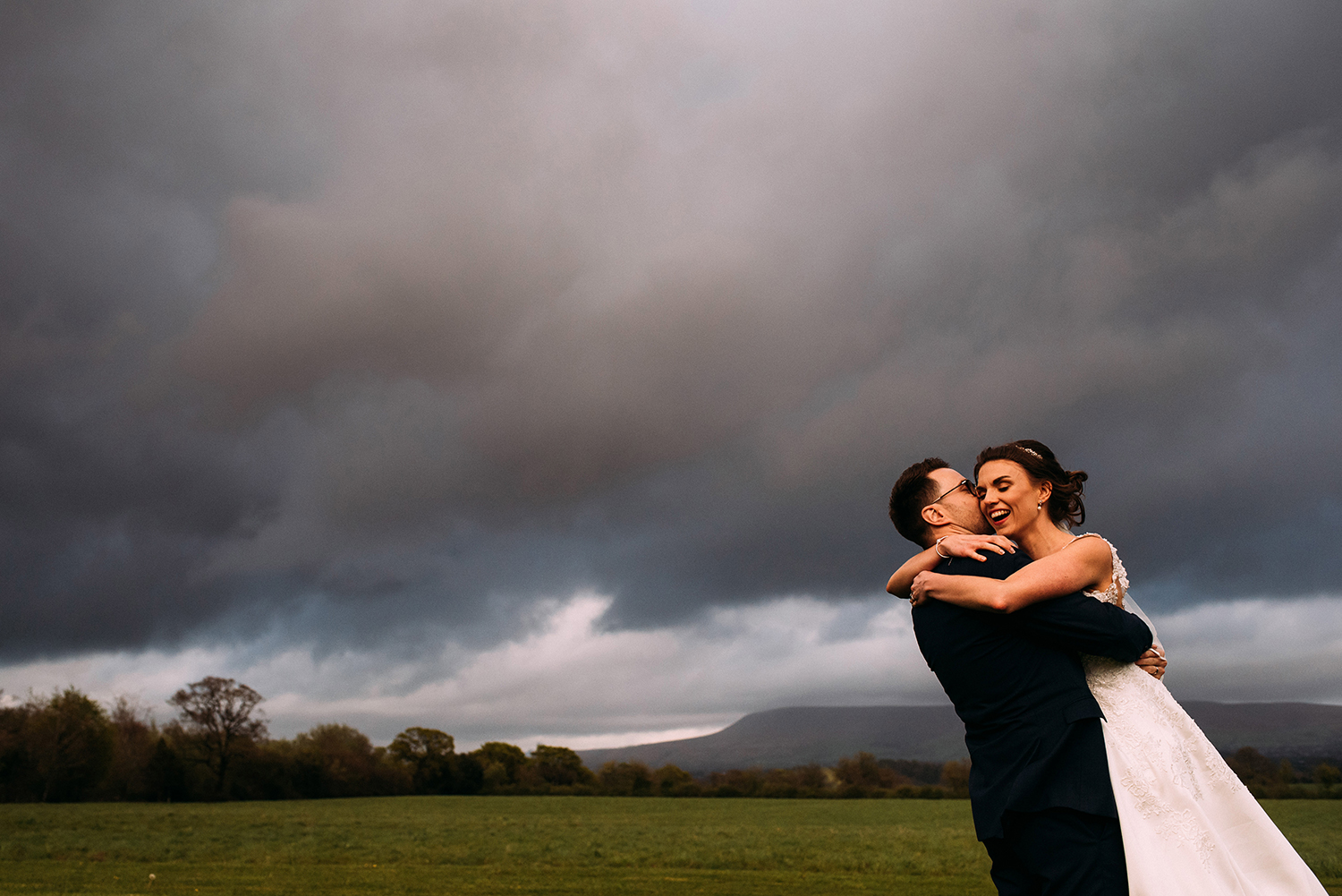Bride and groom at the Out Barn with Pendle hill in the background.