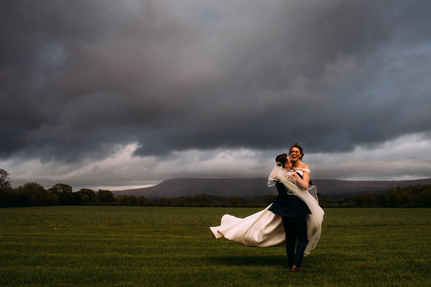 Groom picks up the bride and spins her at the Out Barn with Pendle hill in the background.