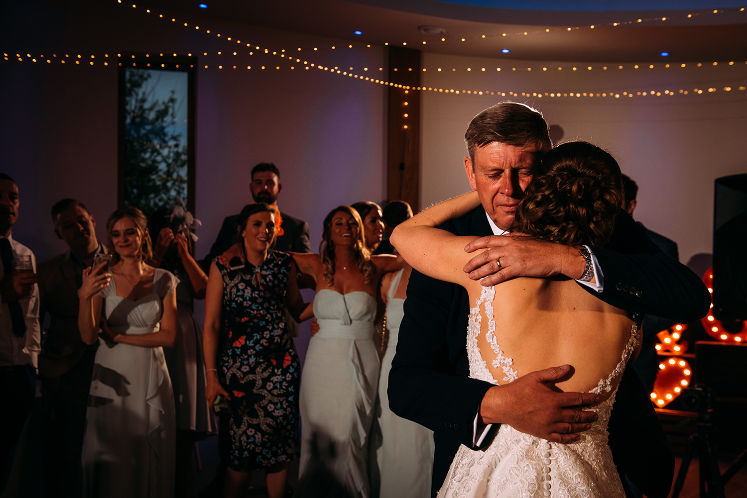bride and her father have an emotional hug