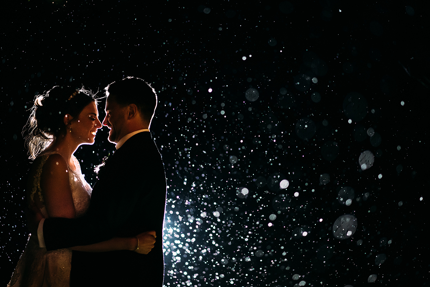 Night time portrait of the bride and groom in the rain at night