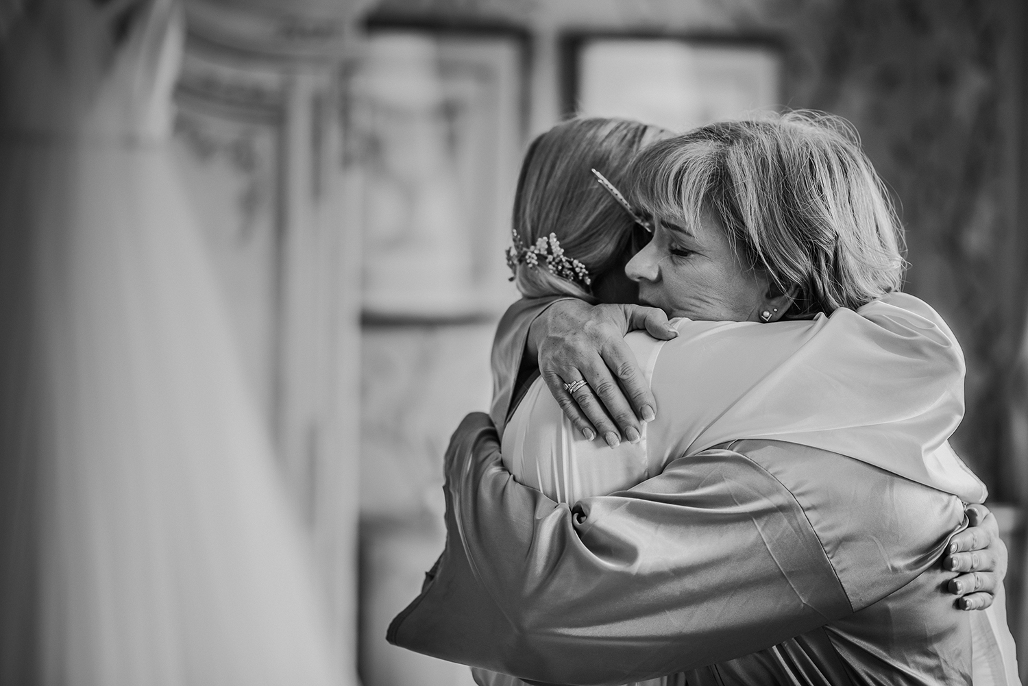 Bw photo of bride's mum giving her a hug in the lodge at Eaves hall