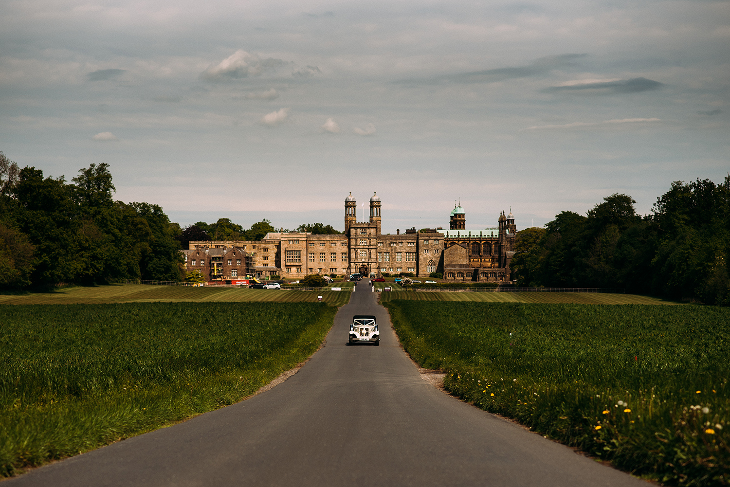 bride and grooms car drives away from Stonyhurst