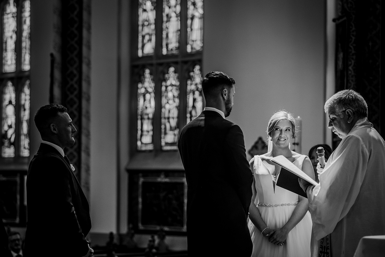bw photo of bride smiling at groom in church