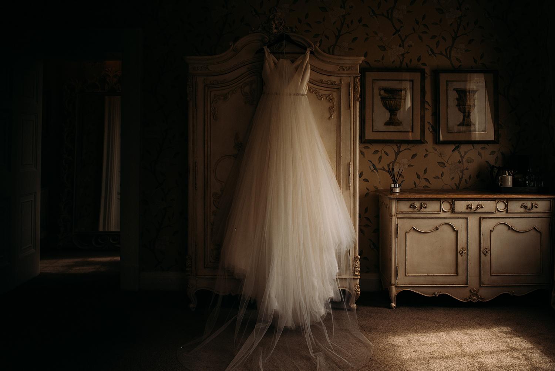 the wedding dress hanging up on the wardrobe