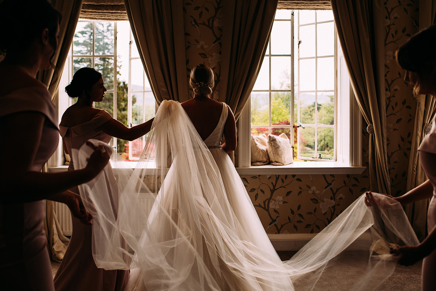 bridesmaids fitting the veil in nice window light