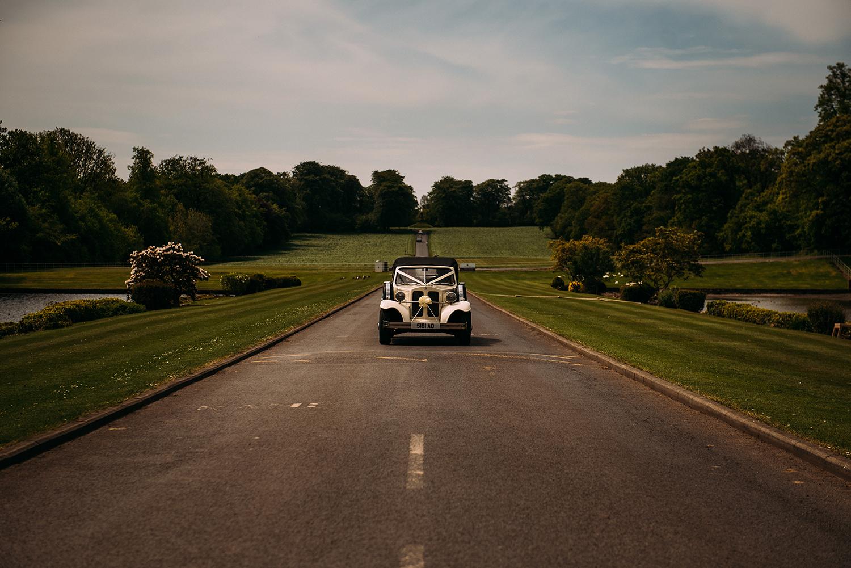 wedding car coming down the long drive way at Stonyhurst