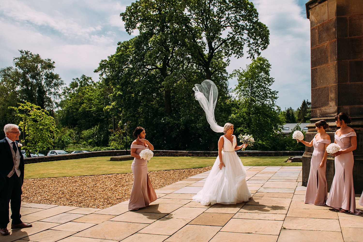 brides veil blowing as she stands with dad and bridesmaids outside church