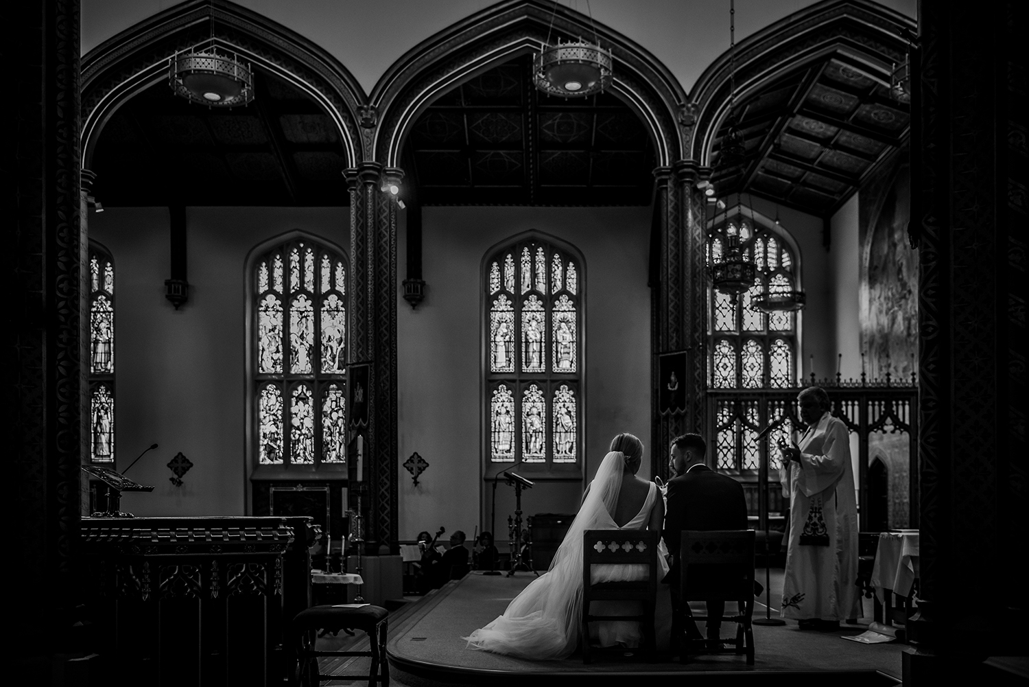 bw photo taken from behind the bride and groom in church