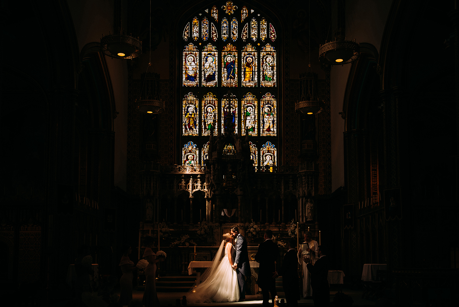 first kiss in church below a huge stained glass window and in amazing light