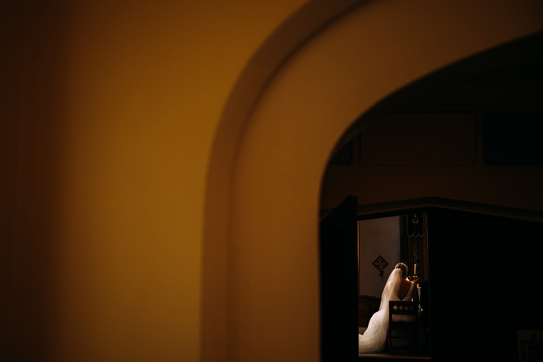 bride sat in church, taken from through a doorway behind her