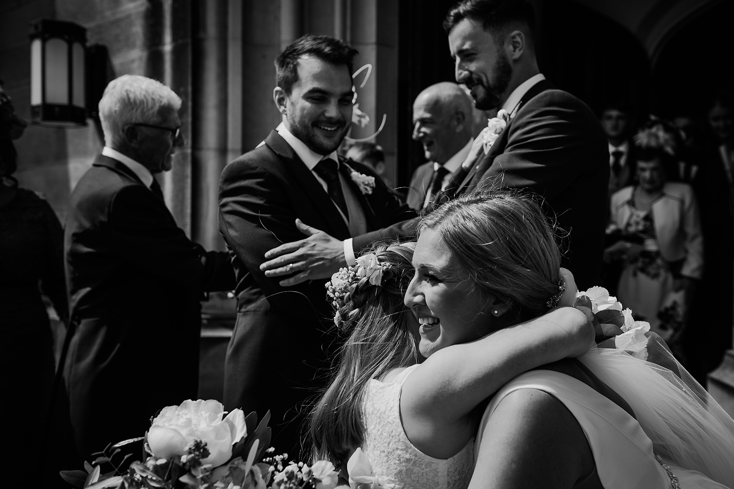 bw photo of bride and groom hugging guests