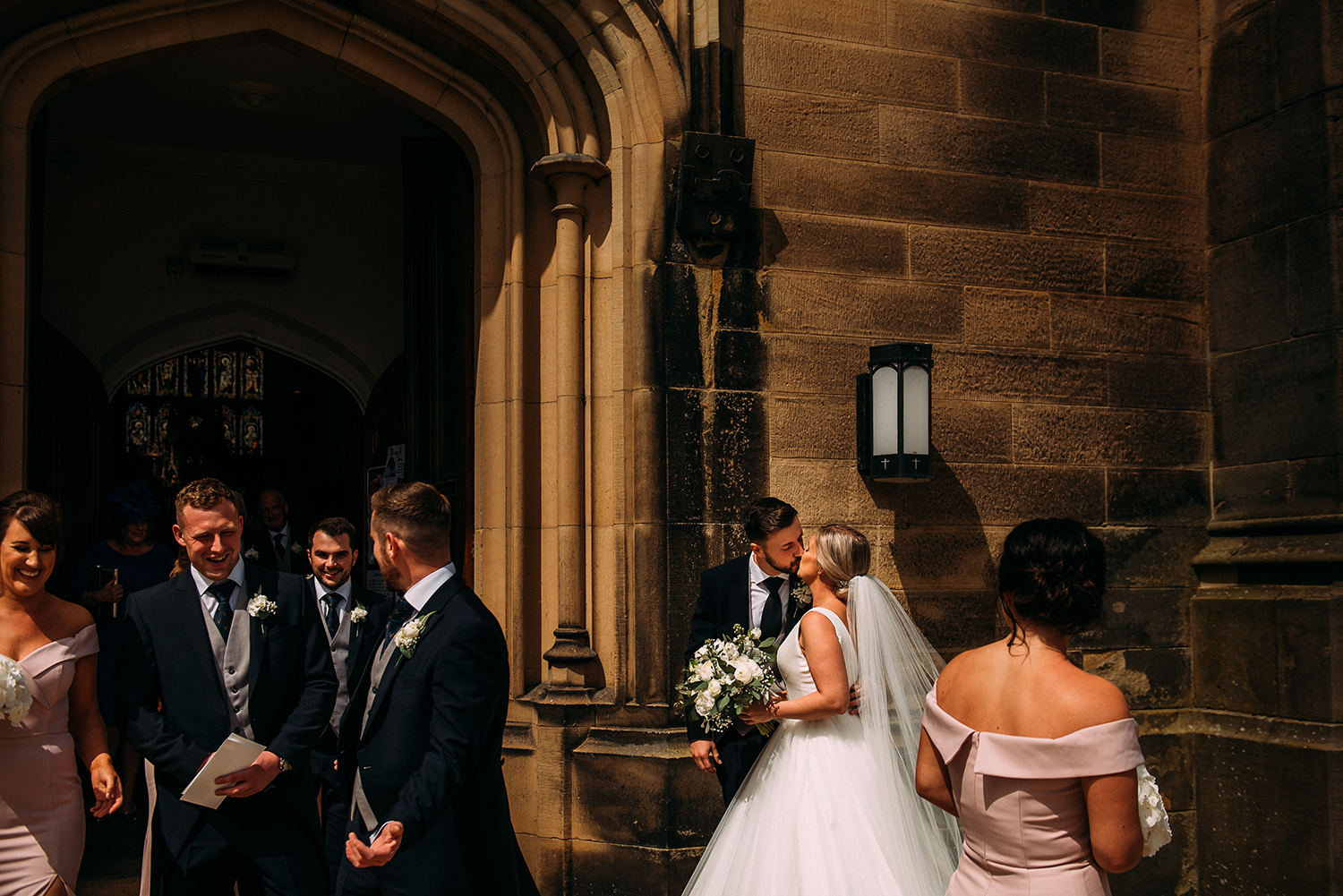 bride and groom kiss as their friends come out of church