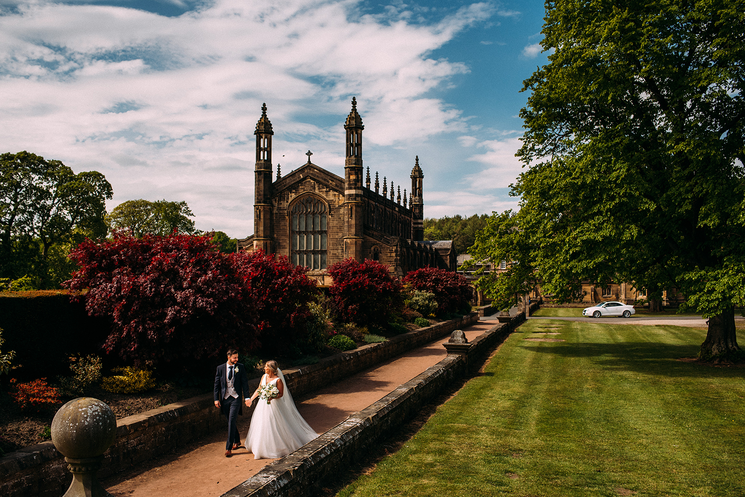 bride and groom walk away from church towards a pond