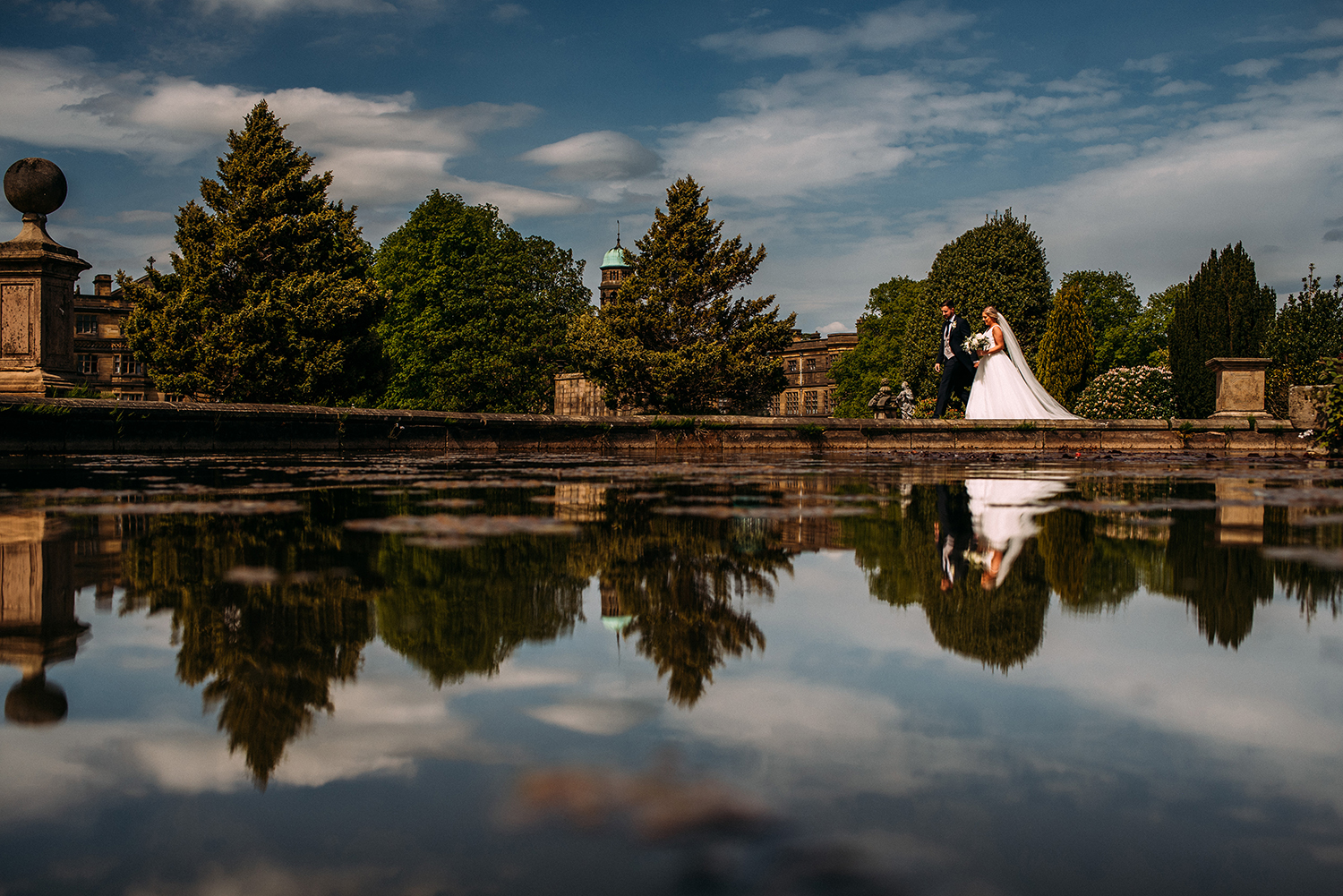 bride and groom walk around a large pond