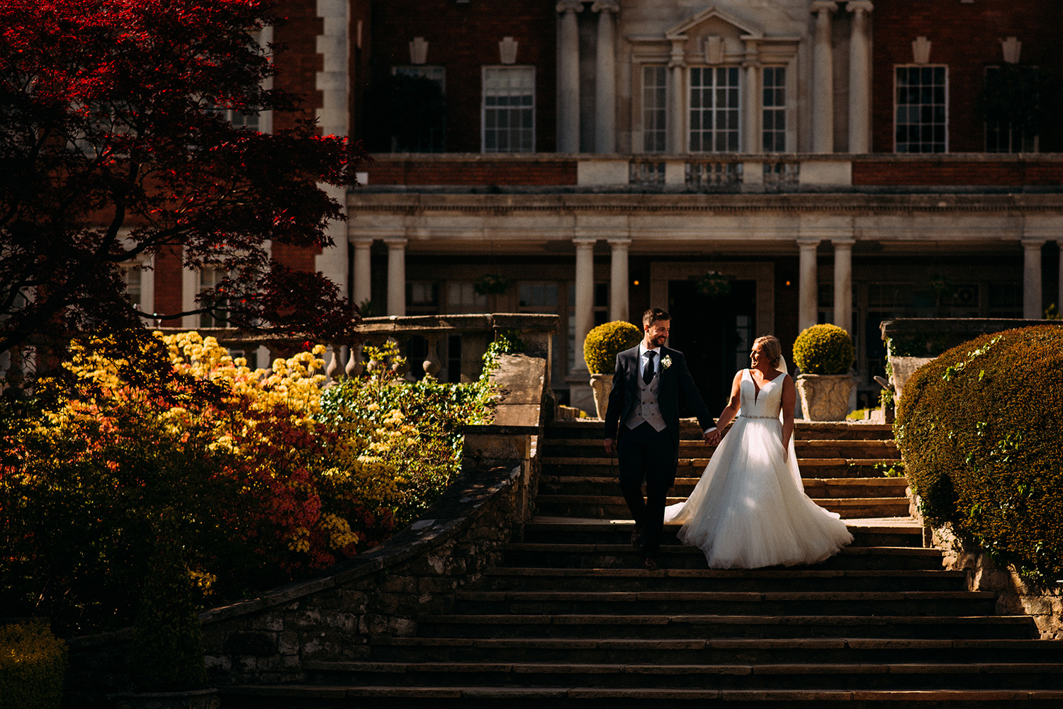 bride and groom walking down the steps at Eaves Hall