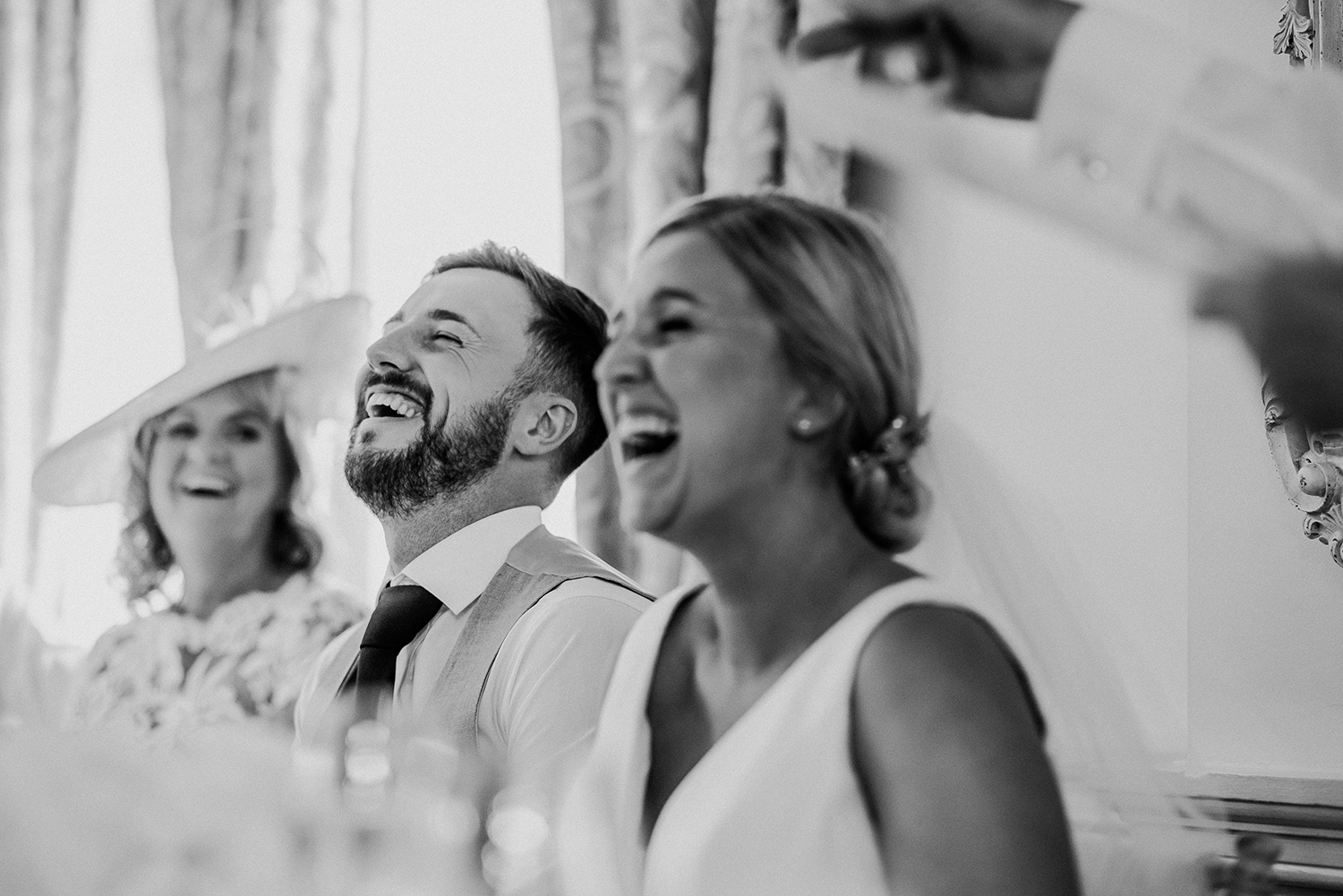 bw photo bride and groom laugh during the speeches