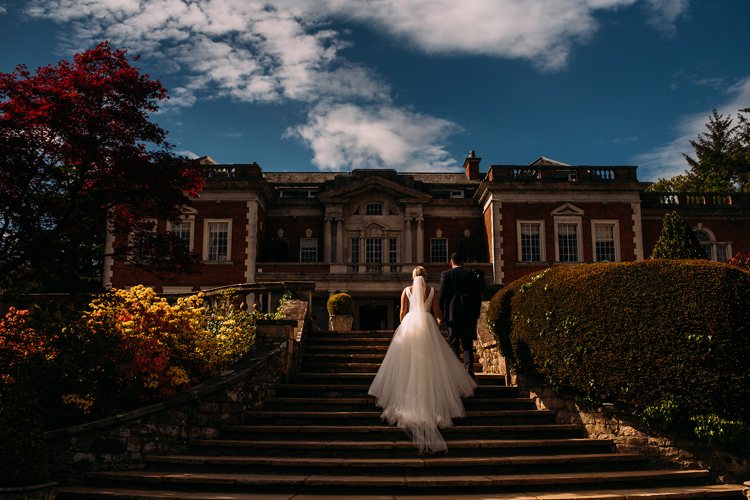 Bride and groom walk back up the steps at Eaves hall