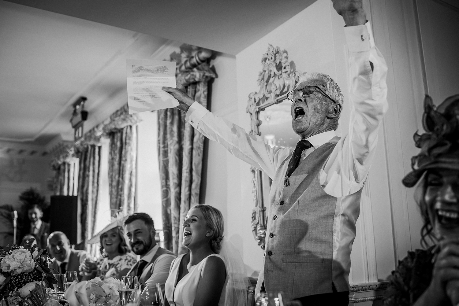 bw photo father of the bride cheers during the speeches