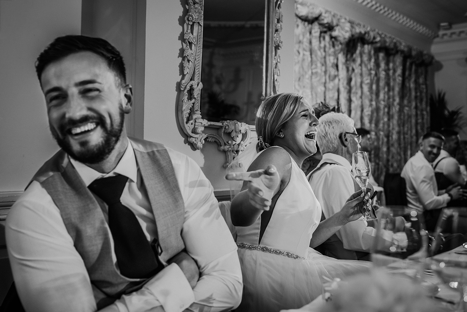 black and white photo of the bride and groom laughing