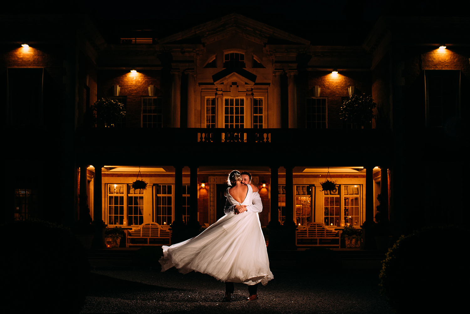 bride and groom hug and spin in front of Eaves hall at night