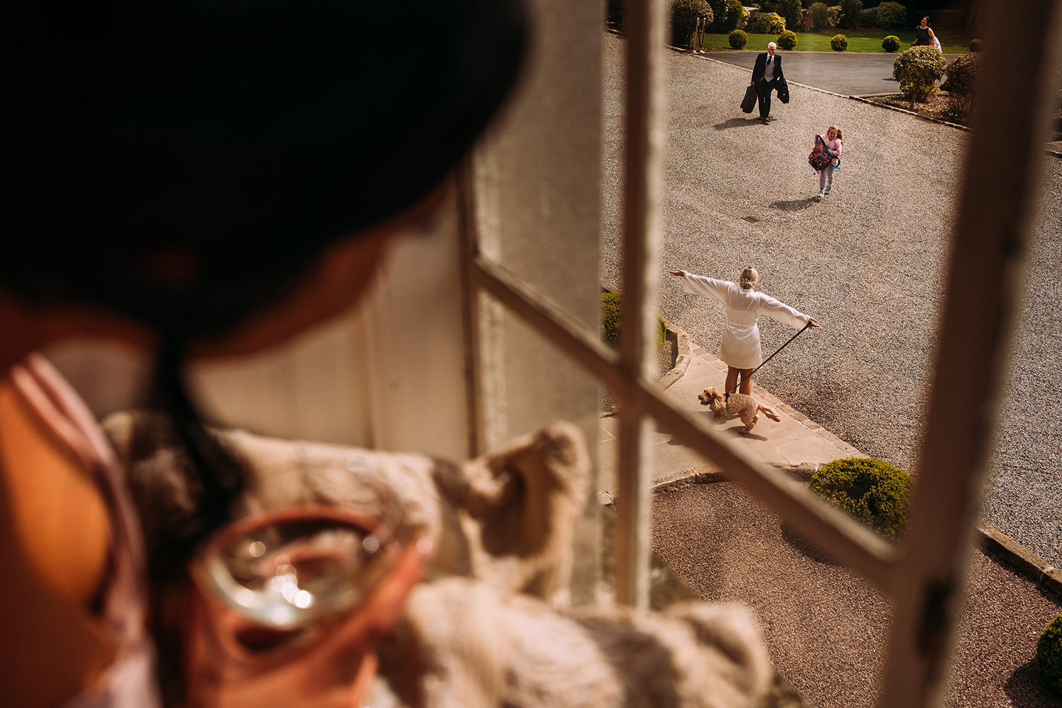 bridesmaid looks out of the window of Eaves hall at the bride hugging her friend down below