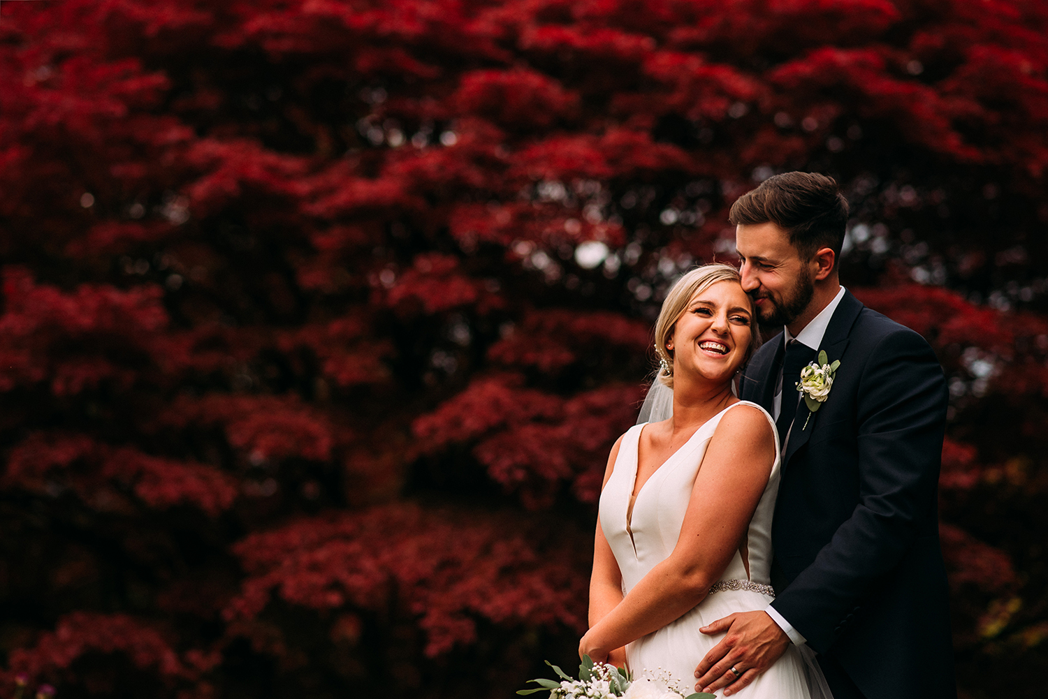 bride and groom in front of the red leaves at Eaves hall