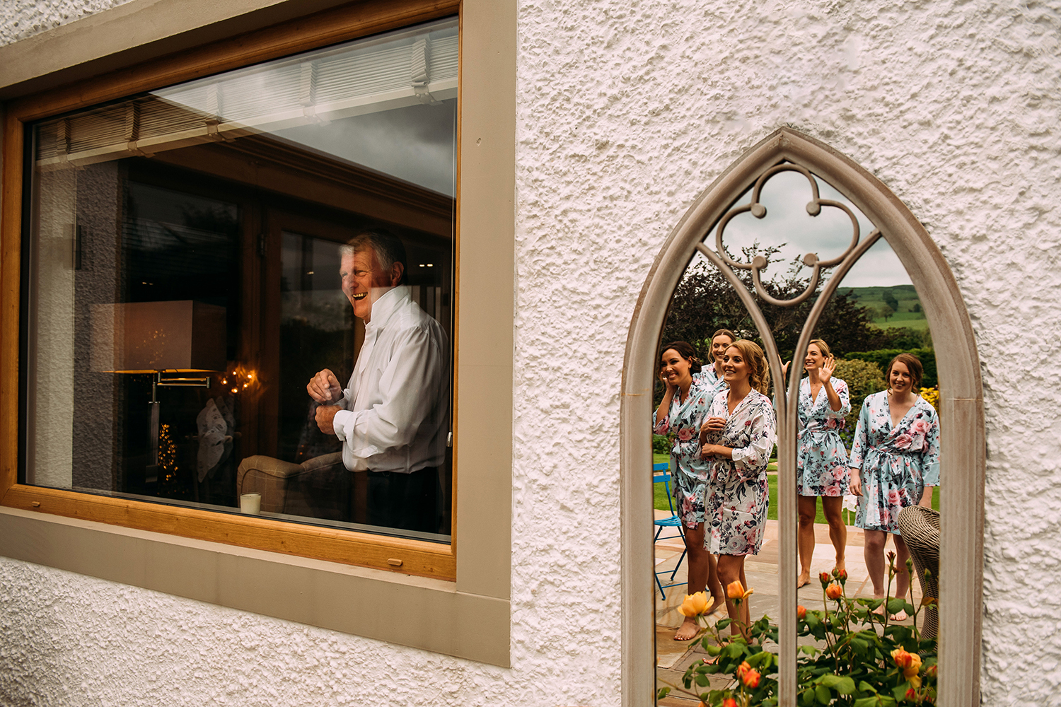 brides father laughs at the bridesmaids - you can see their reflection in the mirror