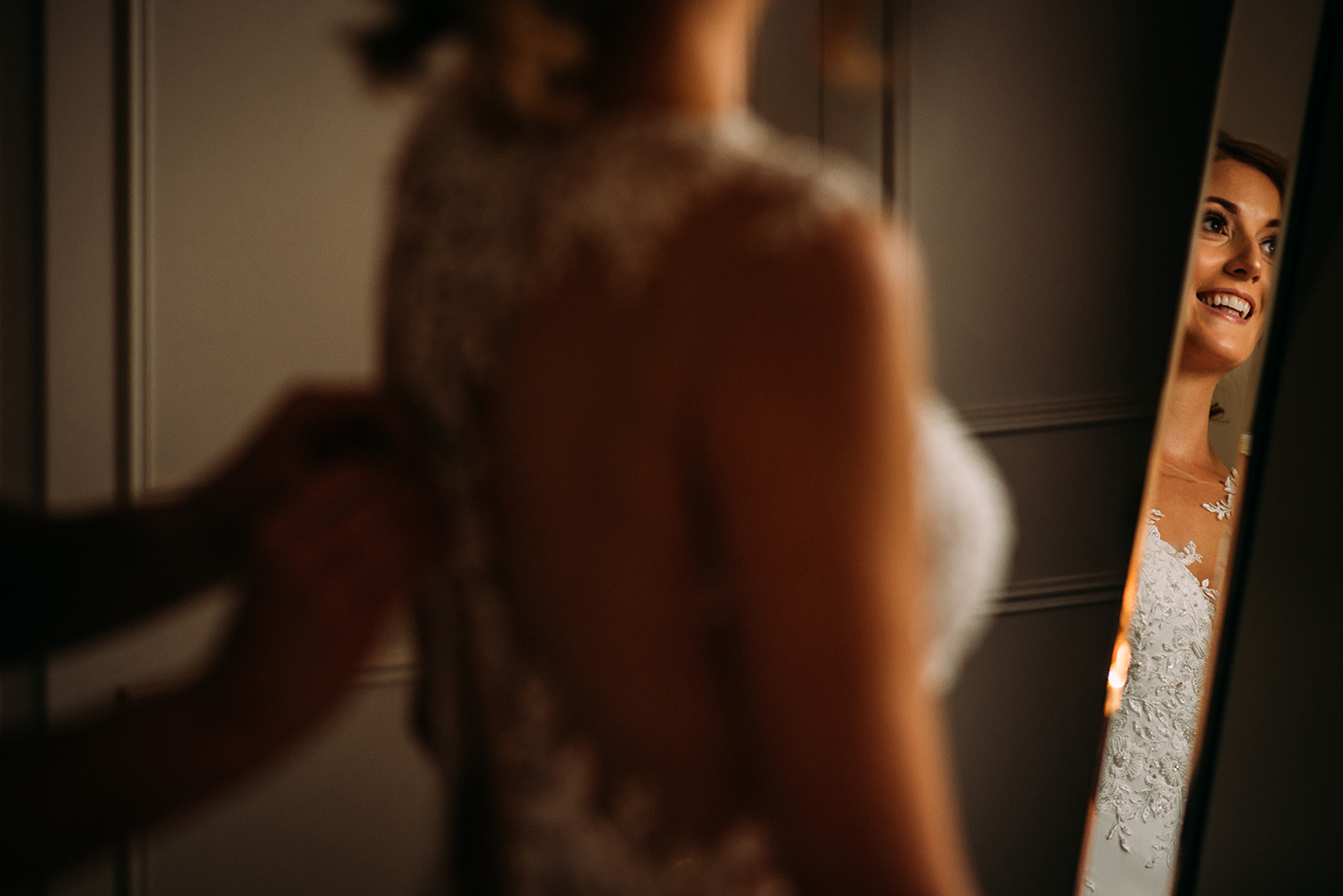 bride having dress fastened, slight reflection of her smile in the mirror