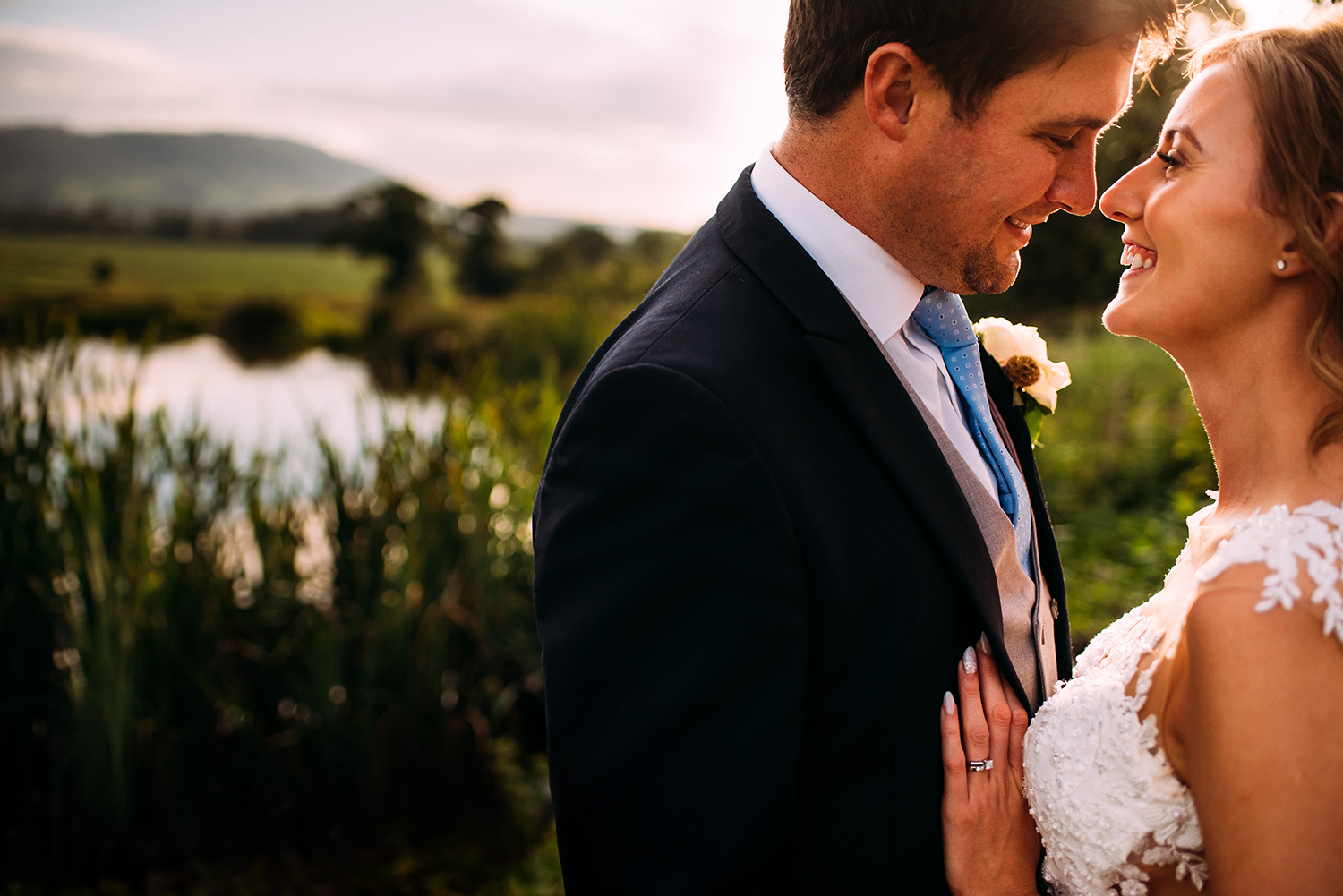 bride and groom by the water in sunlight