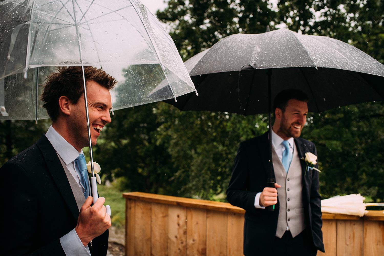 groomsmen greeting guests with umbrella's at Bashall Barn