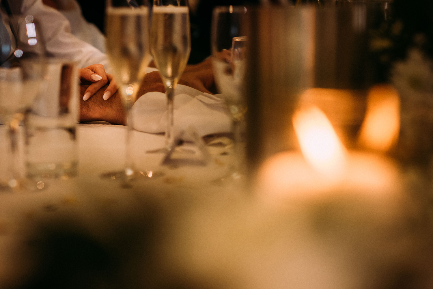 detail of the bride and groom holding hands during the speeches at Bashall Barn