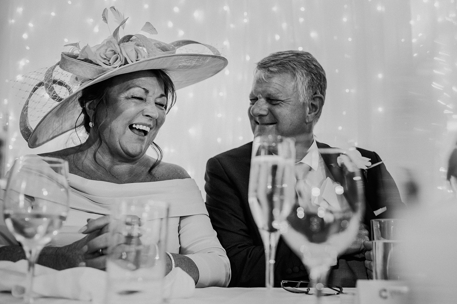 bw photo of brides father and grooms mother laughing at Bashall Barn