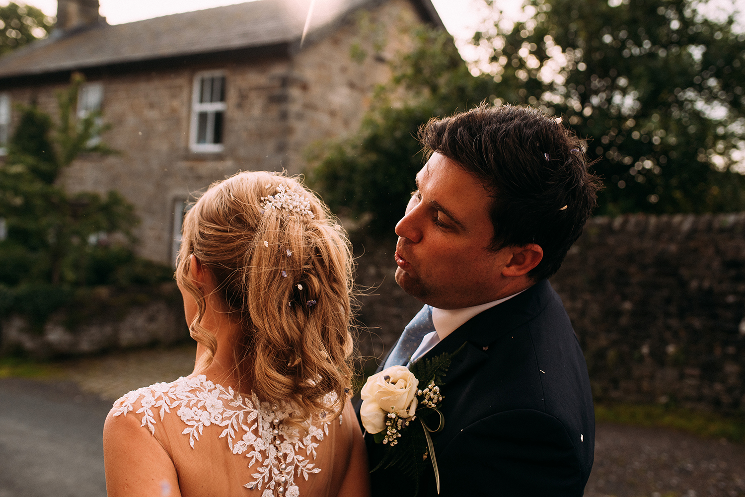 groom picks confetti out of brides hair